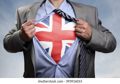 Businessman in classic superhero pose tearing his shirt open to reveal t shirt with the British union jack flag concept for european referendum, patriotism, freedom and national pride