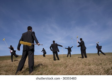 businessman cleaning the field with a broom (some sharp, some with motion blur)