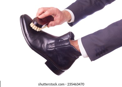 A businessman cleans leather shoes with brush shoe in his hand