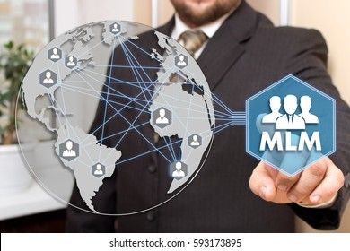 The businessman clicks the button MLM on the touch screen .The concept of multi-level marketing.