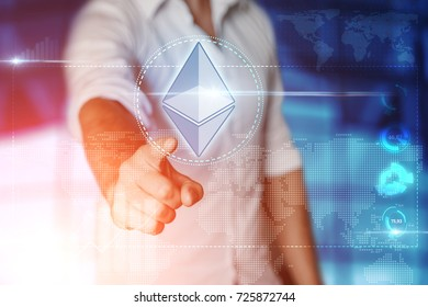 """Businessman clicks on a virtual screen and selects """"ETHEREUM"""". Blue background. Business concept. Mixed media"""