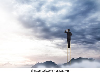 Businessman climbing on a ladder over mountain looking ahead