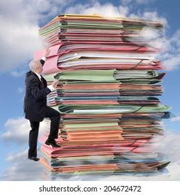 businessman climbing pile of endless paperwork (digital composite)