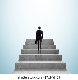 businessman climbing to stairs on blue background