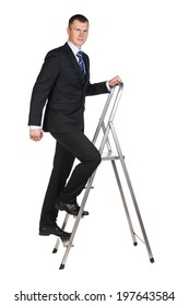 Businessman climbing up a stepladder with his gaze focused on camera . Isolated against a white background