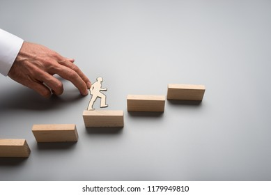 Businessman climbing up the steps to success and advancement in a conceptual image with paper silhouette cutout of a man and a male hand helping him climb over wooden steps.