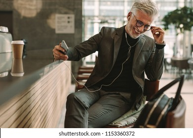 Businessman in coffee shop listening to music on earphones. Mature businessman sitting at cafe in earphones and holding a mobile phone.