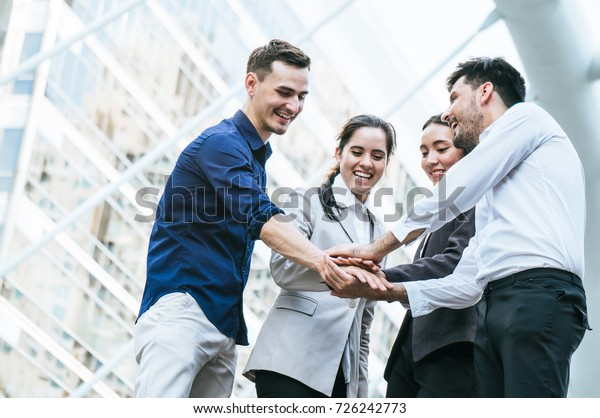 Businessman with colleagues stacking hand to cooperate on building background outdoor in city