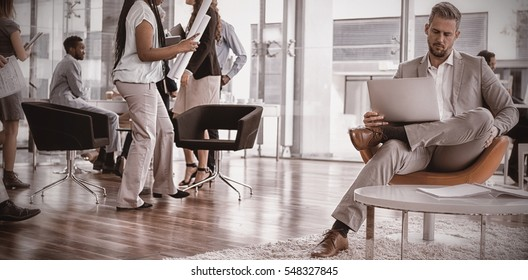 Businessman with colleagues using laptop while sitting on chair in office