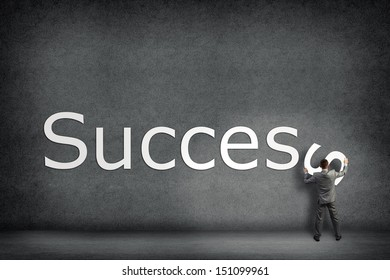 Businessman collects on the wall the word success, places the letter on the wall