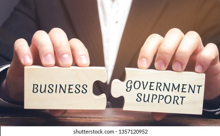 Businessman collects puzzles with the words Business and government support. Tax relief. Protection of manufacturers in the domestic market and promotion in foreign markets. Exemption from taxes.