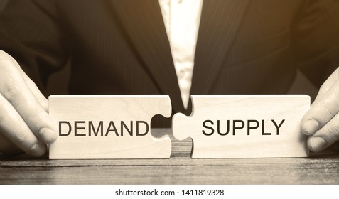 Businessman collects wooden puzzles with the word Demand and Supply. The concept of the labor market. Economic theory, relationships. Business and commerce. Competitiveness and quality level. Law