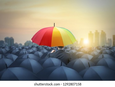 businessman with colorful rainbow umbrella among others, unique different concept