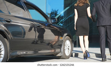 Businessman coming to the car and opens the door for the beautiful young woman. Man uncover door of automobile for female passenger. Girl get from the auto and leaves with her boyfriend. Slow Motion.