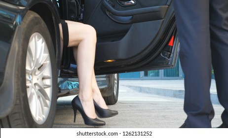 Businessman coming to car and opens door for young woman. Man uncover door of automobile for female passenger. Businesswoman get out from the auto and leaves with her colleague to office building.
