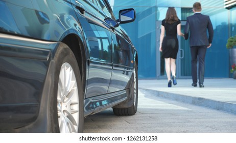 Businessman coming to car and opens door for beautiful young woman. Man uncover door of automobile for female passenger. Girl get out from auto and leaves with her boyfriend to modern office building.