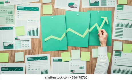 Businessman composing a successful financial chart with arrow going up, he is using green paper cuts, eco business and financial success concept