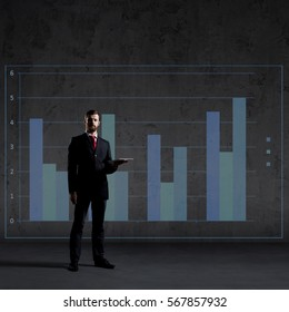 Businessman with computer tablet standing over column diagram background. Business, office, career, job concept.  - Shutterstock ID 567857932