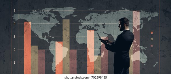 Businessman with computer tablet standing over diagram. World map background. Business, globalization, capitalism concept.