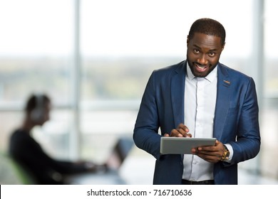 Businessman with computer tablet. Young executive smile and looking straight with digital tablet. Young manager in office on blurred background.