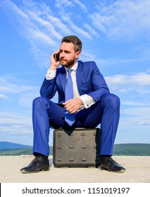 Businessman concentrated sit on briefcase blue sky background. Take minute to analyze. Business decision concept. Businessman formal suit call business partner while wait meeting deal handover.