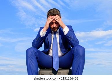 Businessman concentrated sit on briefcase blue sky background. Take minute to analyze. Businessman formal suit thinking about business while wait meeting deal handover. Business decision concept.