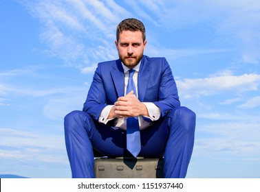 Businessman concentrated sit on briefcase blue sky background. Businessman formal suit thinking about business while wait meeting deal handover. Take minute to analyze. Business decision concept.