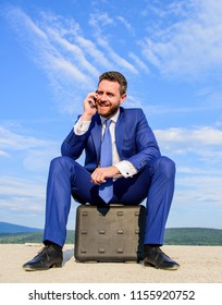 Businessman concentrated sit on briefcase blue sky background. Business decision concept. Take minute to analyze. Businessman formal suit call business partner while wait meeting deal handover.