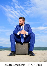 Businessman concentrated sit on briefcase blue sky background. Take minute to analyze. Business decision concept. Businessman formal suit thinking about business while wait meeting deal handover.