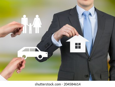 Businessman and a concept of a dream life: a family, a car and a house.