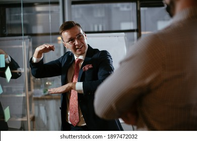Businessman in conference room use sticky notes on glass wall. Handsome businessman making a business plan
