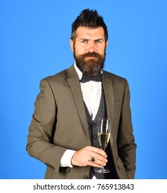 Businessman with confident face holds sparkling wine. Manager with beard holds glass of champagne. Man in classic suit on blue background. Christmas corporate party concept.