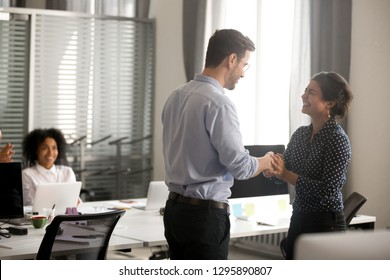 Businessman congratulate indian female successful worker shaking hands in office. Surprised hindu millennial woman feels happy proud getting promotion or reward handshaking with director company boss