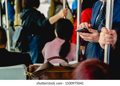 Businessman consulting his mobile phone while traveling by subway to take advantage of time.