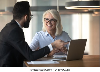 Businessman consulting mature businesswoman client about loan, insurance or investment, using laptop, pointing at screen, young man helping senior colleague with software, employee presenting project