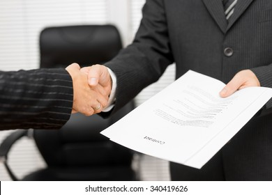 Businessman with contract in his hand is handshaking with business partner