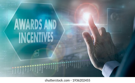 A businessman controlling a futuristic display with a Awards and Incentives business concept on it.