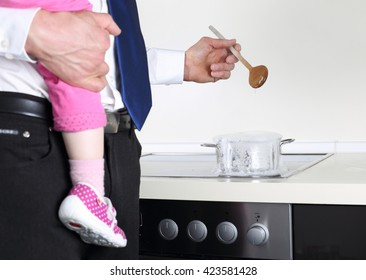 A Businessman cooking with Baby on arm