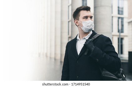 Businessman and coronavirus epidemic. Close up portrait of young business man in a disposable facial mask. A man defends himself against covid 19 on the big city street. Modern buildings at background