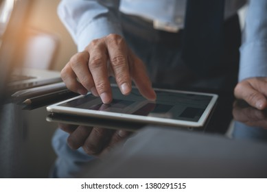 Businessman or corporate man, finance analyst zooming in digital tablet computer reviewing business report with digital diagram, financial graph while working on laptop computer in office, close up