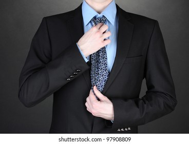 businessman correcting a tie on black background