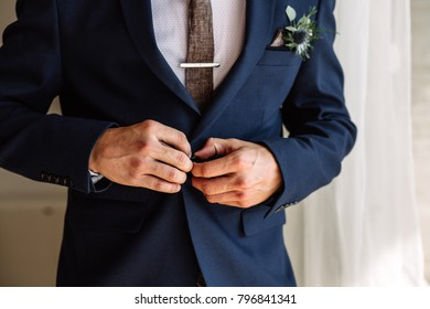 Businessman corrects buttons on his jacket, hands close-up, dressing, man's style, correcting sleeves, preparing for the wedding