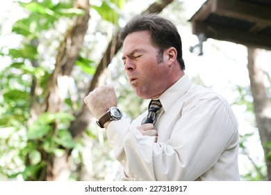 Businessman coughing from the flu, a cold, or other illness, in outdoor environment.