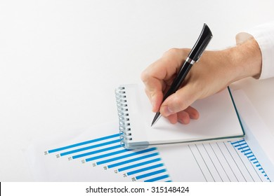 Businessman counting losses and profit working with statistics, analyzing financial the results on white background. Copy space
