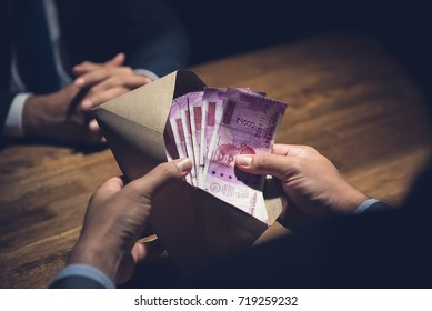 Businessman counting money, Indian Rupee currency, in the envelope just given by his partner after making an agreement in private dark room - loan, bribery and corruption scam concepts