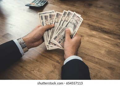 Businessman counting money, Japanese yen banknotes, at wooden table - Shutterstock ID 654557113