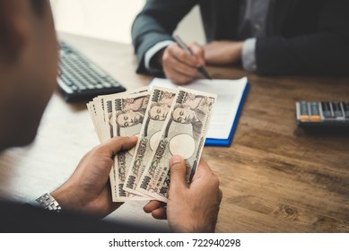 Businessman counting money, Japanese yen currency, while making contract agreement with partner - loan, bribery and corruption concepts