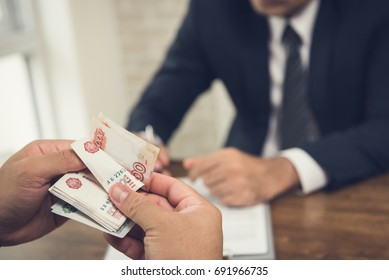Businessman counting money, Russian ruble currency, while making an agreement contact with his partner in the office - loan and financial concept
