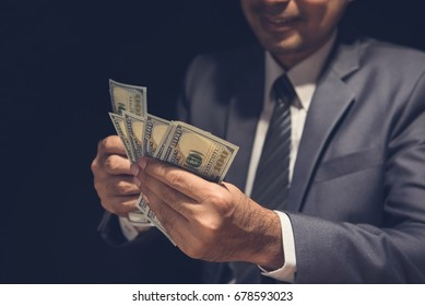 Businessman counting money, US dollar currency, in the dark -  venality and corruption concepts