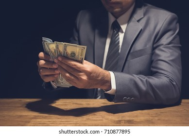 Businessman counting money, US dollar currency, in dark private room -  venality and corruption concepts